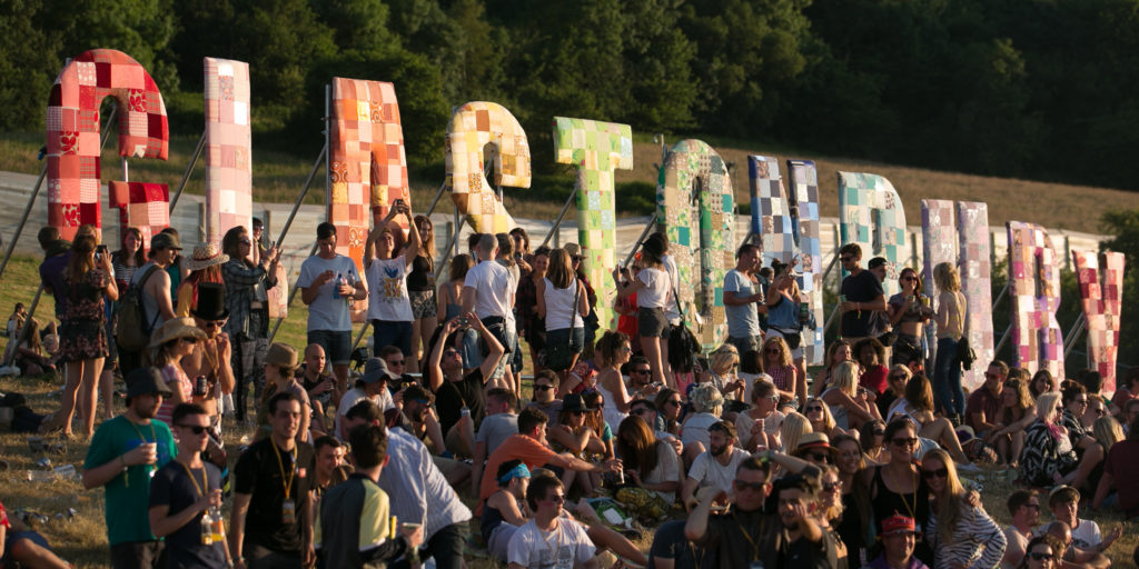 GLASTONBURY, ENGLAND - JUNE 25: People gather to watch the sun set at Worthy Farm in Pilton on the first day of the 2014 Glastonbury Festival on June 25, 2014 in Glastonbury, England. Gates opened today at the Somerset dairy farm that plays host to one of the largest music festivals in the world. Tickets to the event, which is now in its 44th year, sold out in minutes even before any of the headline acts had been confirmed. The festival, which started in 1970 when several hundred hippies paid £1, now attracts more than 175,000 people. (Photo by Matt Cardy/Getty Images)