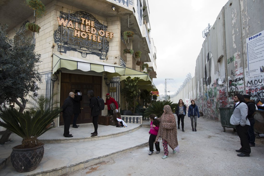 "People pass by the ""The Walled Off Hotel"" and the Israeli security barrier in the West Bank city of Bethlehem, Friday, March 3, 2017. The owner of a guest house packed with the elusive artist Banksy's work has opened the doors of his West Bank establishments to media, showcasing its unique ""worst view in the world."" The nine-room hotel named ""The Walled Off Hotel"" will officially open on March 11. (AP Photo/Dusan Vranic)"